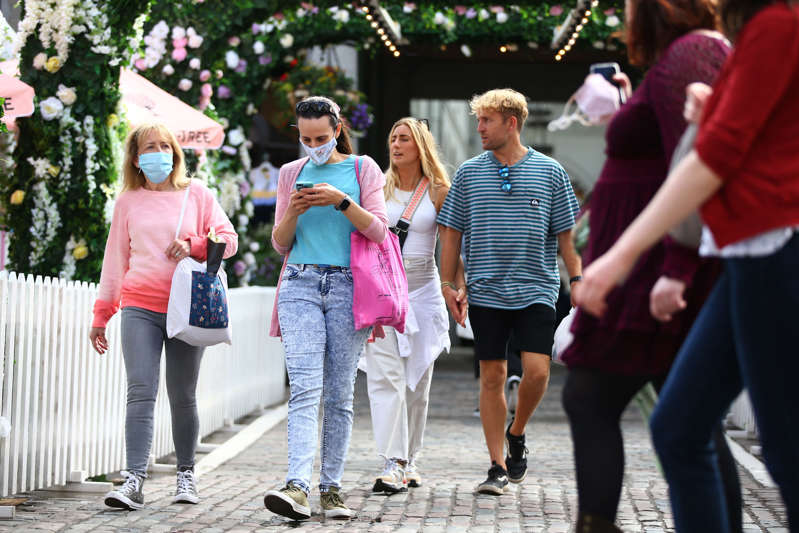 People wear face masks while shopping at Covent Garden on July 4, 2021 in London, England. (Photo by Hollie Adams/Getty Images)