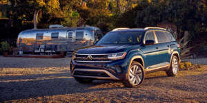 a car parked on the side of a dirt road: If you've been holding out for a three-row EV SUV, Volkswagen has one coming. Can this Atlas-sized crossover help more people convert?