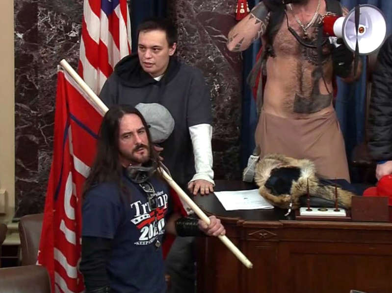 a man holding a baseball bat: In this file image from US Capitol Police video, Paul Allard Hodgkins, 38, of Tampa, Fla., front, stands in the well on the floor of the Senate on 6 January, 2021, at the Capitol in Washington.  - AP