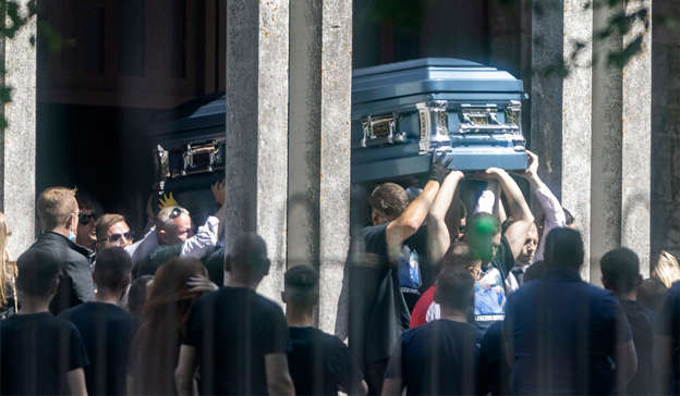 a group of people standing in front of a building: The remains are carried from St Mary's Priory church at the funeral of Dean Maguire on Friday afternoon. Pic: Collins Dublin