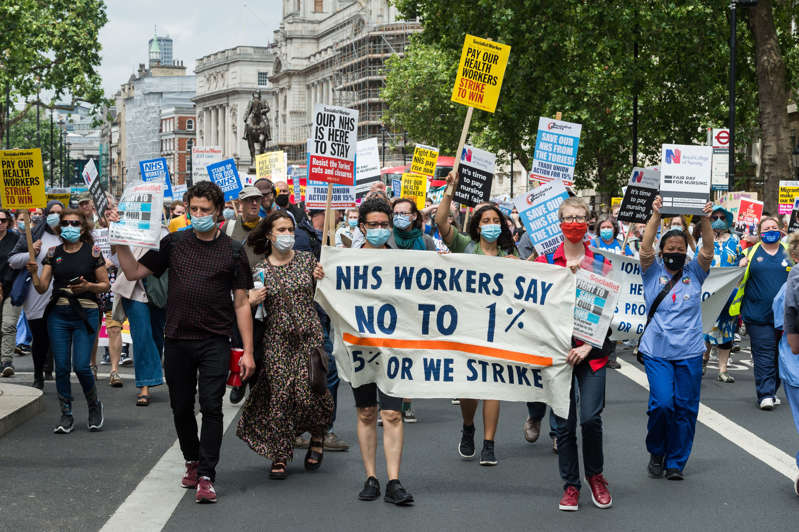 LONDON, UNITED KINGDOM - JULY 03: NHS staff march through central London during a protest demanding a 15% pay rise for healthcare workers, focus on patient's safety and an end to privatisation as part of a national day of action coinciding with the 73rd birthday of the NHS in London, United Kingdom on July 03, 2021. (Photo by Wiktor Szymanowicz/Anadolu Agency via Getty Images)