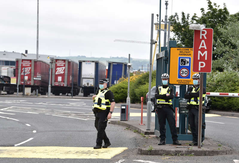 Police officers watch on as Loyalists hold a protest against the Northern Ireland Protocol