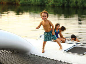 a person holding a frisbee in the water: There's no question that their son Tarzan has a very fitting name. Here, at age 3, he bounded over Thunderbird 's crossbeam at the Rhebergen Multihull Yachts' dock in Amsterdam.