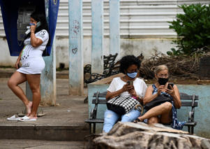 a man and a woman sitting on a bench talking on a cell phone: Women use their phones in Havana on July 14. (Yamil Lage/AFP via Getty Images)