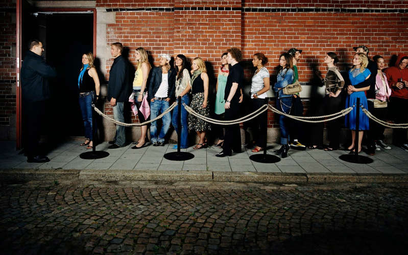 a group of people standing in front of a brick building: Clubs - Patrik Giardino /Getty Images