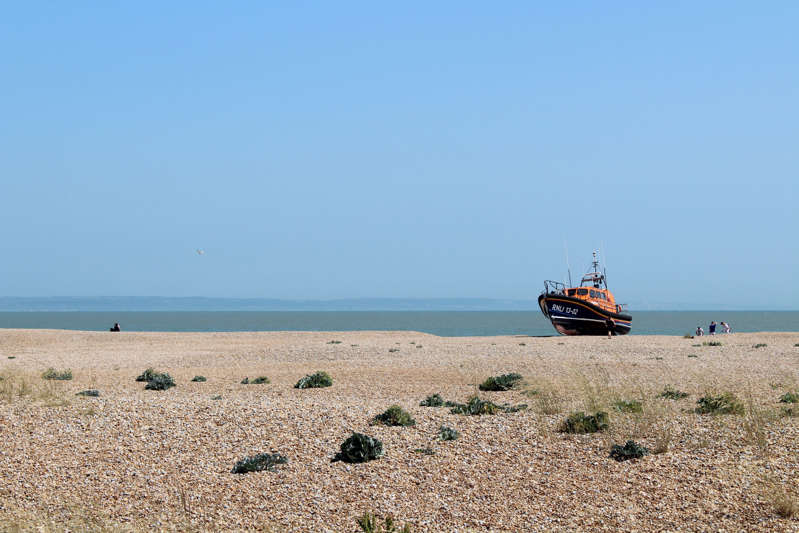 a boat sitting on top of a sandy beach next to the ocean: The Dungeness RNLI lifeboat is shown on the beach on 22 July, 2021. (Rory Sullivan)