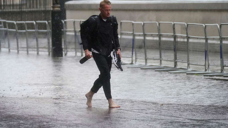 a man in a wet suit is walking in the rain: One man thought it would be a good idea to take his shoes off as large puddles formed in central London