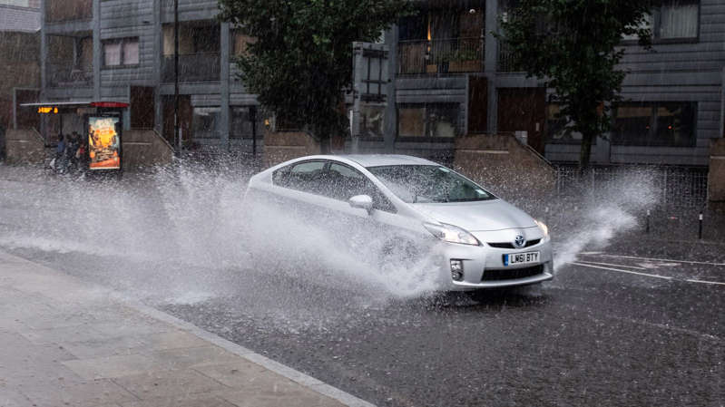 a car parked on the side of a road: Heavy rain could cause hazardous conditions for drivers