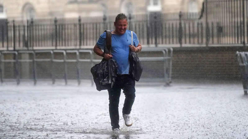 a man standing on a sidewalk: Heavy rain fell on central London as the Met Office issued amber warnings for the South
