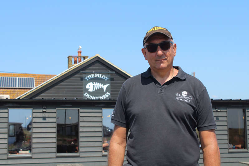 a man standing in front of a building: Niko Miaoulis is pictured in front of the pub he owns in Dungeness. (Rory Sullivan)