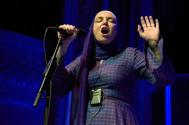 Sinéad O'Connor standing on a stage: Sinead O'Connor performs at August Hall