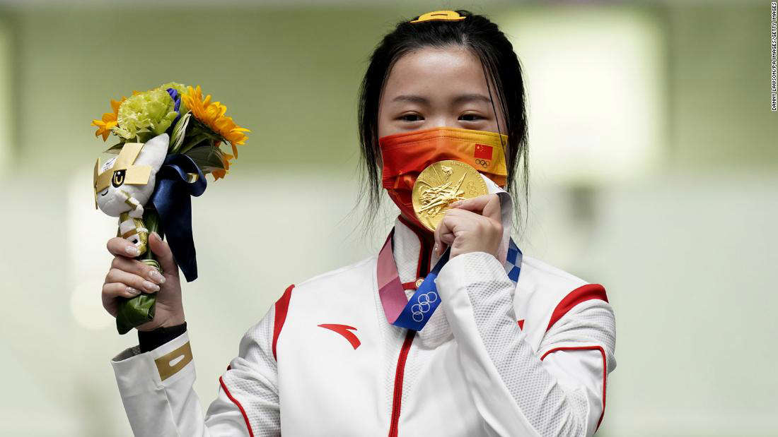 a person wearing a costume: China's Yang Qian celebrates with her gold medal after winning the 10m Air Rifle Women's Final on the first day of the Tokyo 2020 Olympic Games.