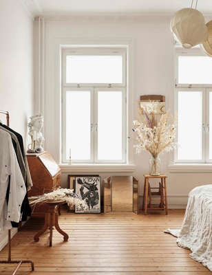a living room filled with furniture and a large window: Every piece of furniture and lighting in the bedroom of this Swedish apartment, including this cabinet, is a secondhand find. Photo: Andrea Papini | Styling: Andrea Papini, Ida Magntorn | House of Pictures | Living Inside
