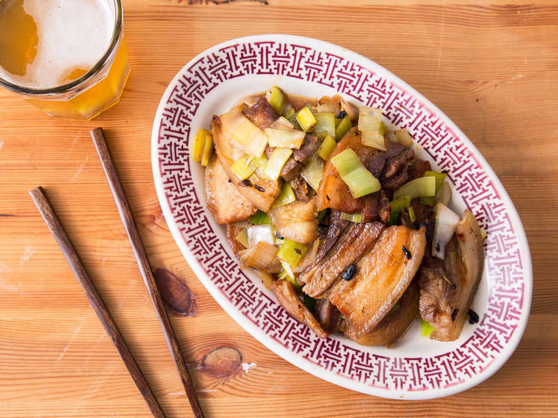 a plate of food sitting on top of a wooden table: Sichuan Twice-Cooked Pork Belly