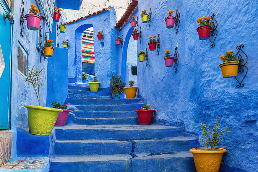 """Slide 5 of 24: Nestled in the Rif mountains of northern Morocco, this maze of alleyways boast electric shades of blue. There are many theories as to why the town is painted in this way, such as to follow Jewish custom, to keep the mosquitos away, and to represent the cerulean sea, but the full story behind this """"Blue Pearl of Morocco"""" remains a mystery."""