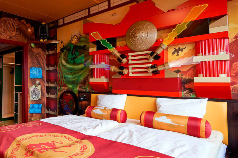 a bedroom with a bed and desk in a room: The Lego Ninjago guest room is just one of the themes offered for accommodations at the new Legoland Hotel in Goshen, New York.