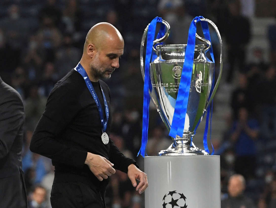 Soccer Football - Champions League Final - Manchester City v Chelsea - Estadio do Dragao, Porto, Portugal - May 29, 2021 Manchester City manager Pep Guardiola walks past the Champions League trophy after the match Pool via REUTERS/Pierre-Philippe Marcou TPX IMAGES OF THE DAY