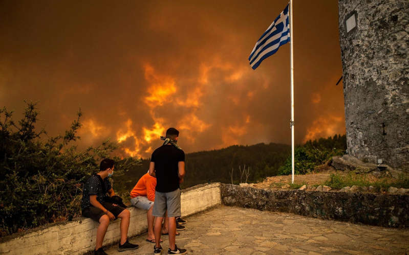 a man riding a bike down a dirt road: Local residents watch a wildfire approaching the village of Gouves on Evia, Greece's second largest Greek island, on August 8, 2021 - AFP
