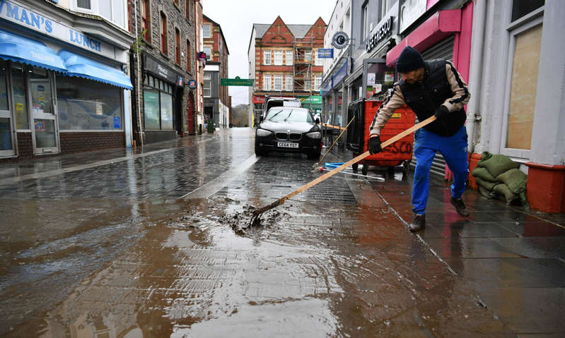 a person walking down the street in the rain: A man cleans up the street in Pontypridd after Storm Dennis caused flooding in February 2020.