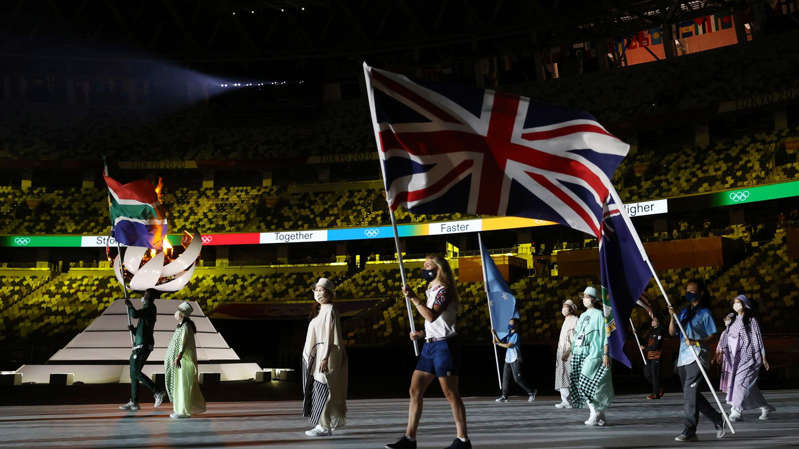 a group of people standing around a plane: Laura Kenny carried the flag at the closing ceremony