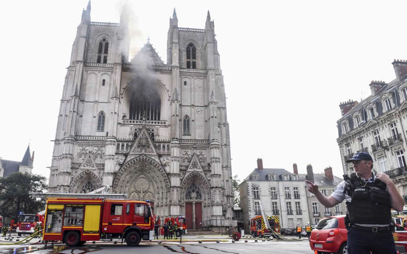 a person standing in front of a building: Firefighters and police officers try to put out the fire at the Saint-Pierre-et-Saint-Paul cathedral in Nantes in July 2020 - SEBASTIEN SALOM-GOMIS/AFP
