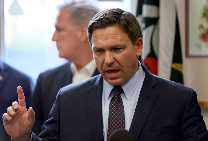 Ron DeSantis wearing a suit and tie: Florida Governor Ron DeSantis' office announced Monday that the Florida Board of Education may act to withhold the salaries of school board officials who choose to go against the governor's executive order and require facemasks in schools. Here, the governor appears at a press conference on August 05, 2021 in Hialeah, Florida.