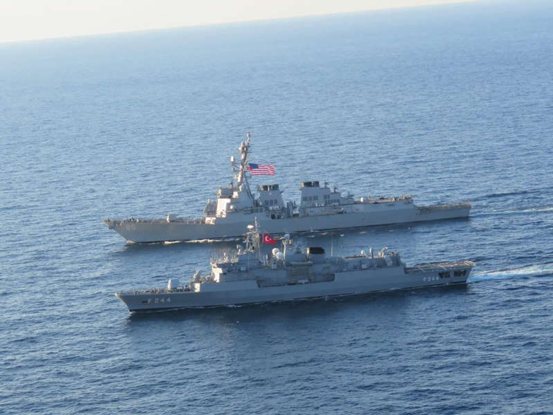 a large ship in a body of water: The guided-missile destroyer USS Roosevelt sailing alongside the Turkish Navy frigate TCG Barbaros in the Black Sea, October 2020.