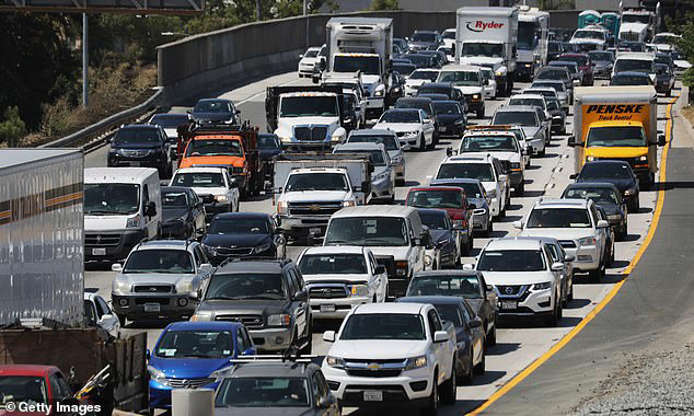 a car driving on a city street filled with lots of traffic: A 2019 federal report found that a VMT tax could help ease road congestion
