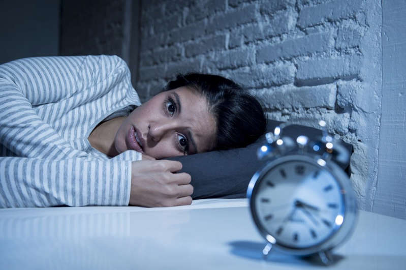 a clock on the side of a building: hispanic woman at home bedroom lying in bed late at night trying to sleep suffering insomnia sleeping disorder or scared on nightmares looking sad worried and stressed