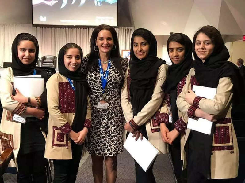 a group of people posing for a photo: The Afghan all-girls robotics team have been offered scholarships at 'incredible universities,' says Oklahoma mother who helped them escape the Taliban