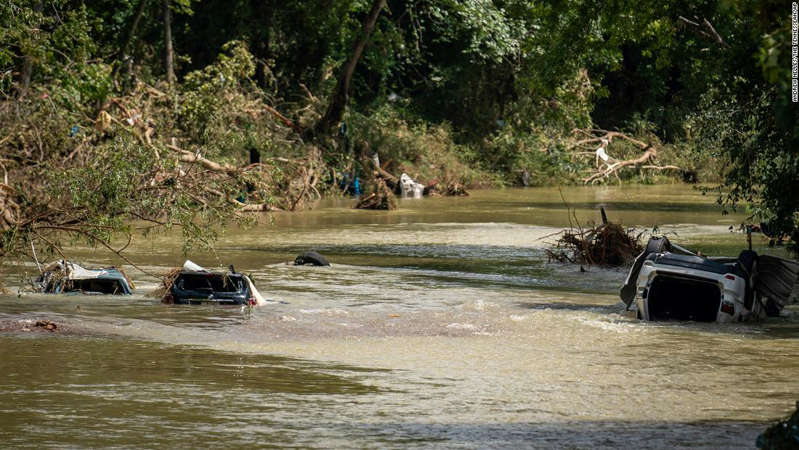 a group of people crossing a river: Vehicles are submerged in Trace Creek as a result of severe weather in Waverly.