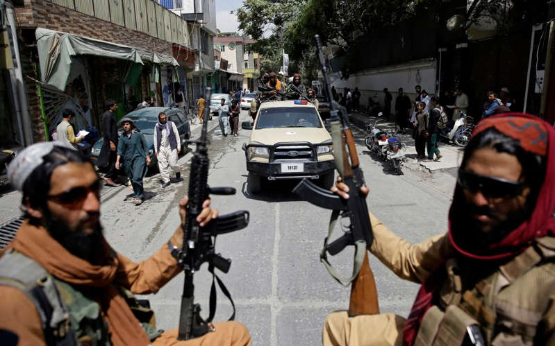 a group of people walking down the street: Taliban fighters on patrol in central Kabul - AP/AP