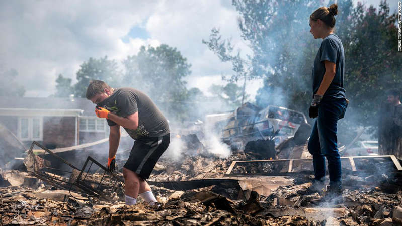 a man that is on fire: Josh Whitlock and Stacy Mathieson look through what is left of their home after it burned following flooding in Waverly, Tennessee.
