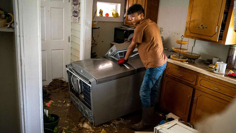 a man standing in front of a refrigerator: Kalyn Clayton, 16, surveys the damaged kitchen of a home while volunteering with his church youth group in Waverly, Tennessee.