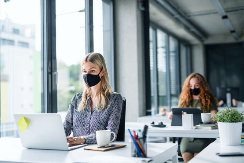 a woman sitting at a table using a laptop: people with face masks back at work or school in office after lockdown