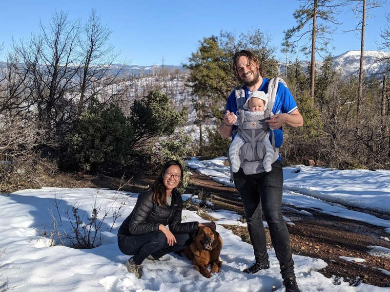 a person and a dog in the snow: Ellen Chung and John Gerrish with their daughter, Miju, and dog, Oski.