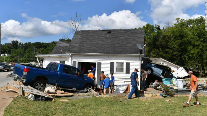 a group of people playing frisbee in a yard: A damaged house is seen Sunday in Waverly, Tennessee.