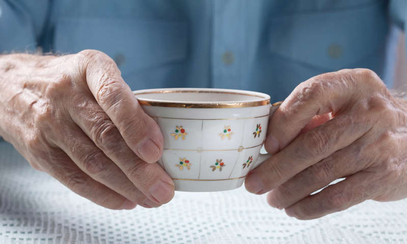 a hand holding a cup of coffee: MailOnline logo
