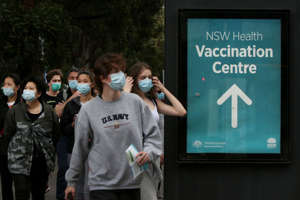 a group of people standing in front of a sign: People arrive to be vaccinated at the New South Wales Health mass vaccination hub in Homebush on August 23, 2021 in Sydney, Australia.