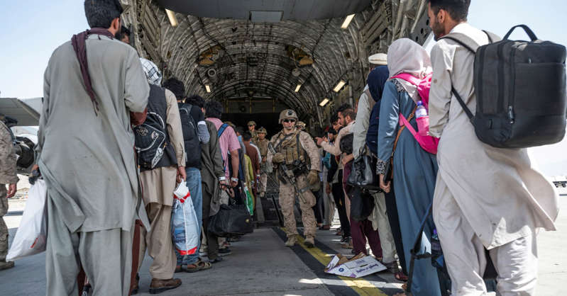 a group of people standing around a bag of luggage: U.S. Airmen and U.S. Marines guide qualified evacuees aboard a U.S. Air Force C-17 Globemaster III at Hamid Karzai International Airport (HKIA), Afghanistan, August 21, 2021.