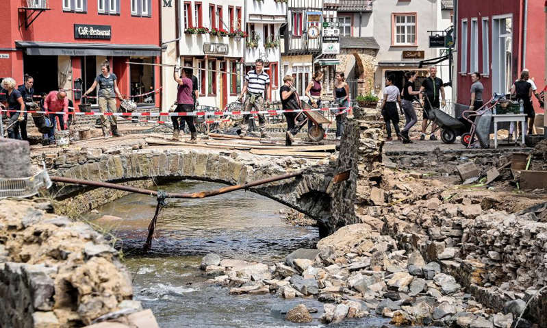 a group of people standing in front of a large rock: Residents clear debris after heavy flooding of the River Erft caused severe destruction in the village of Bad Münstereifel, Euskirchen district, Germany on 20 July. Photograph: Sascha Steinbach/EPA