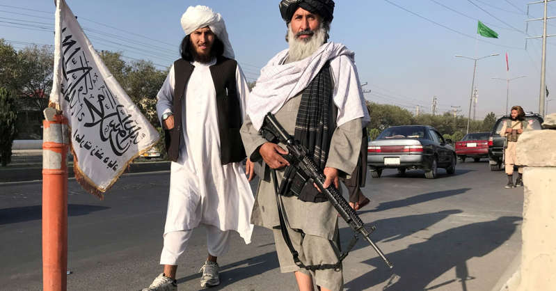 a man and a woman walking down the street: A Taliban fighter holding an M16 assault rifle stands outside the Interior Ministry in Kabul, Afghanistan, August 16, 2021.