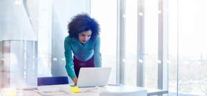 a person sitting at a table using a laptop: 5 Keys To Seeing Business Problems As Opportunities Rather Than Burdens