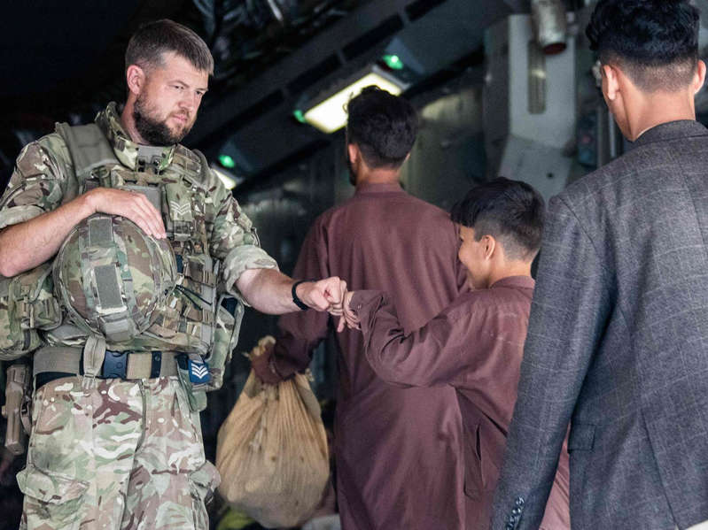 a man in a military uniform: British military handling Afghan refugees at Kabul airport in this MoD picture issued on Tuesday - MOD/AFP via Getty Images