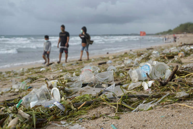a group of people on a beach: For all its attractions, Bali is not without problems, including the mountains of plastic waste that wash up on its beaches. Photo: Getty Images