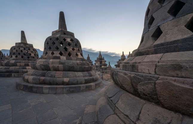 a stone building that has Borobudur in the background: The Indonesian site contending for the best destination prize is not Bali, but Borobudur Temple. Photo: Getty Images