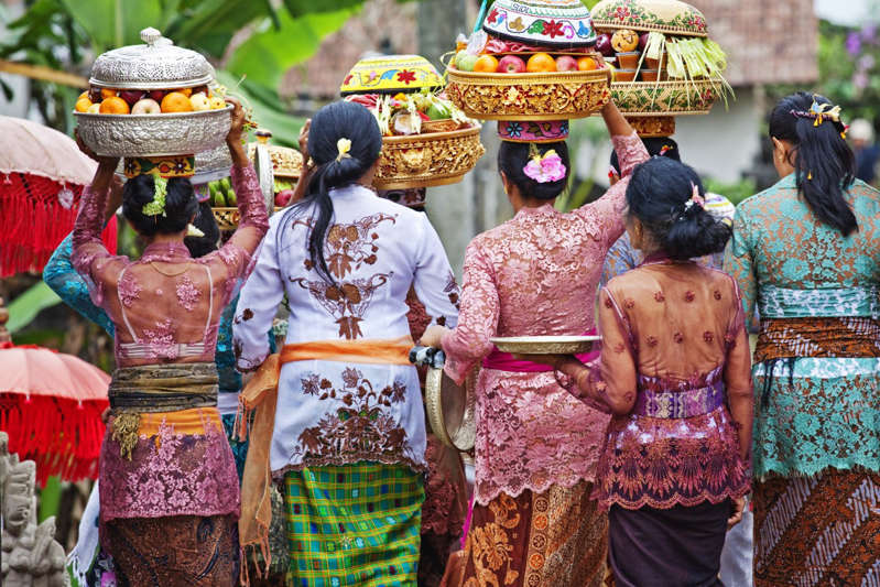 a group of people in costumes: Women carry temple offerings to Pura Gunung Raung Temple near Ubud, Bali, Indonesia's most visited island. Photo: Getty Images