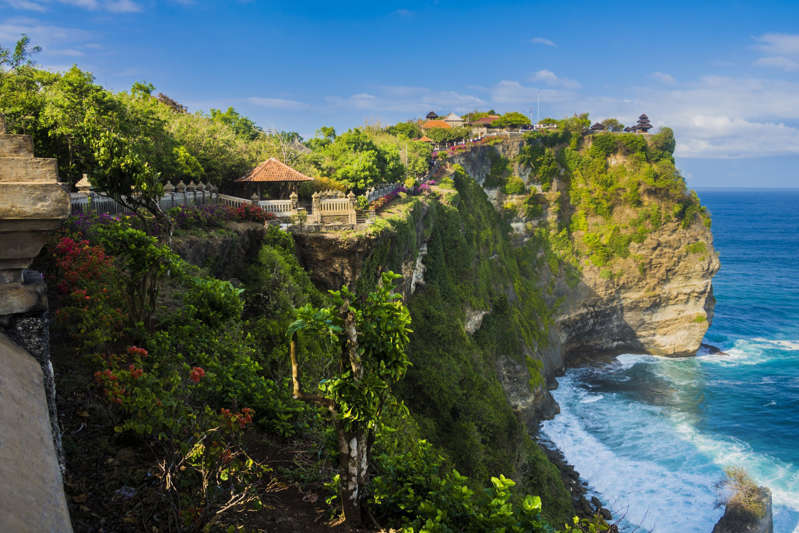 a group of people in a rocky area: Uluwatu Temple in Bali. Photo: Getty Images