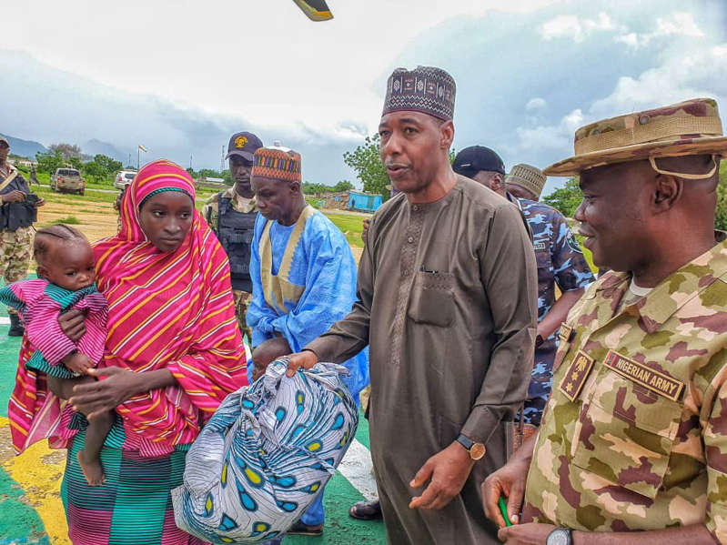 In this photo released by the Borno State government House, Recently freed Chibok School girl and her daughter, left, is welcomed by Borno State Governor, Babagana Zulum, centre, in Maiduguri Nigeria. Seven years after Boko Haram extremists abducted more than 270 schoolgirls in northeast Nigeria, two of the more than 100 still being held by the rebels returned this month, renewing the hope of parents who have all but given up on the long wait for the return of their children. Some of the affected parents said they remain hopeful that they will reunite with their children in Borno State, where the Boko Haram insurgency has lasted for more than a decade. (Borno State House via AP)