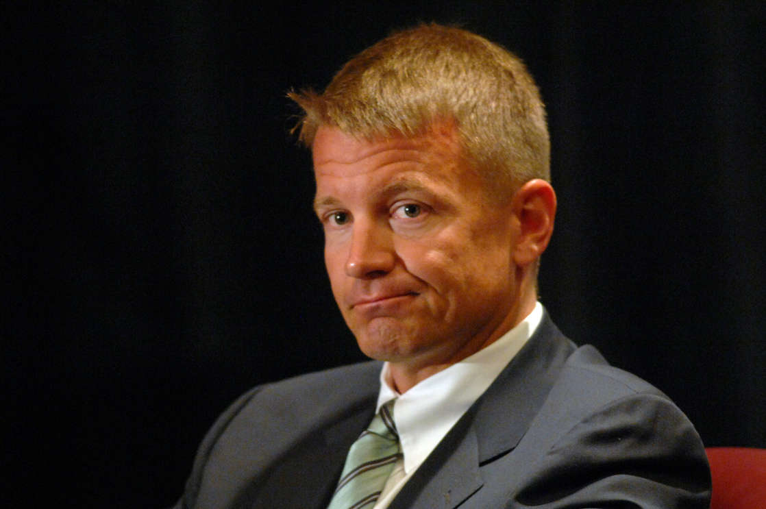Erik Prince wearing a suit and tie: Blackwater CEO and founder Erik Prince listens during a panel discussion on protecting people and physical security hosted by North Carolina Technology Association in Cary, N.C., Thursday, June 7, 2007.